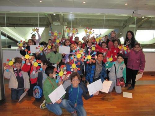 الأطفال يحملون شهادة حضور ورشة العمل، والنماذج التي صنعوها بأيديهم للمجموعة الشمسية